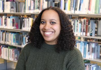 Semira Mesfin in front of stacks at Minneapolis Central Library