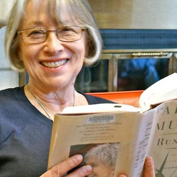 Older woman wearing glasses is smiling while reading book by the fireplace