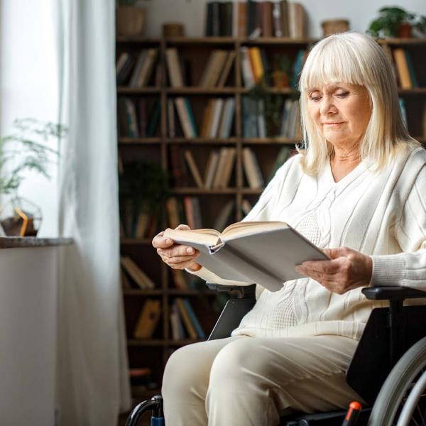 A woman in a wheelchair reading by the window