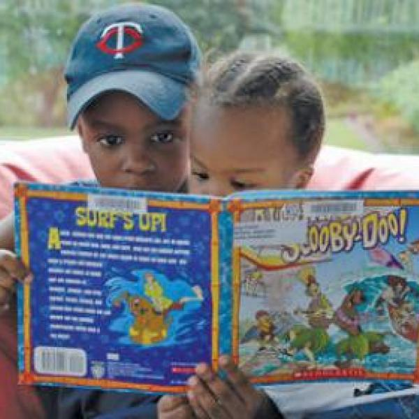 Two small children sitting on a been bag chair reading a kids book together
