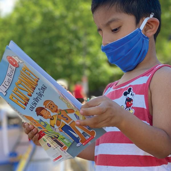Boy with a face mask reading a kids book by the library bike