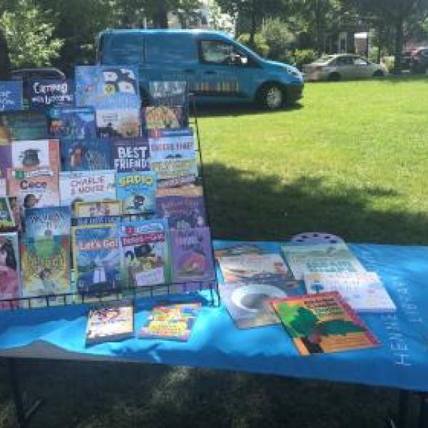 Table in the park with children's books and the Library Van parked near by