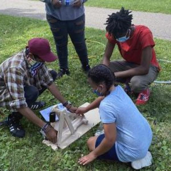 A group of kids siting on the grass and working on a STEM project during summer learning in the park